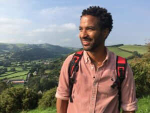 Sean Fletcher TV presenter walking Offa's Dyke Path with hills in the background