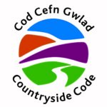 A circular Welsh logo on white background with 'The Countryside Code' and 'Cod - Cefn - Gwald' in black text around the outside of the ring. In the inner ring an abstract landscape clipart with a streak of blue, orange and purple in the sky and a green streak with a white lane/river going into the distance.