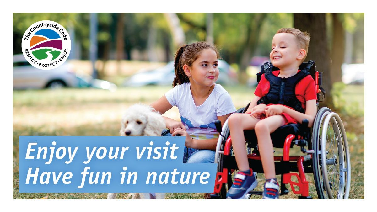 Two children, one using a wheelchair with a dog smile at each other. They're in an area with grass and trees. Text reads: Enjoy your visit. Have fun in nature. In the top left there's circular English logo on white background with 'The Countryside Code' and 'Respect - Protect - Enjoy' in black text around the outside of the ring. In the inner ring an abstract landscape with a streak of blue, orange and purple in the sky and a green streak with a white lane/river going into the distance.